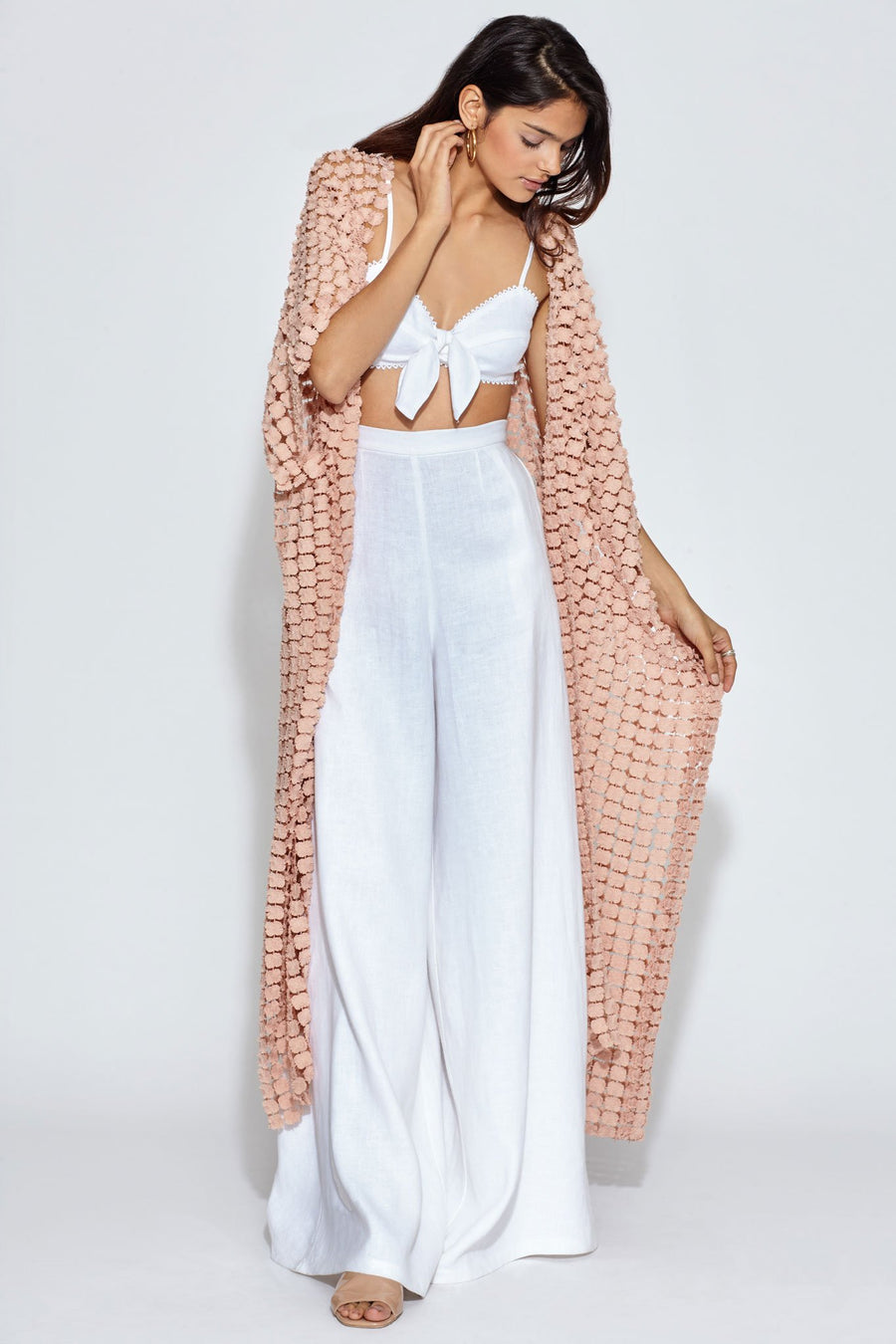 This is a photo of a woman wearing a white linen bralette with white linen wide leg pants. On top of the bralette and pants, she is wearing a dusty pink, dandelion lace cover-up.
