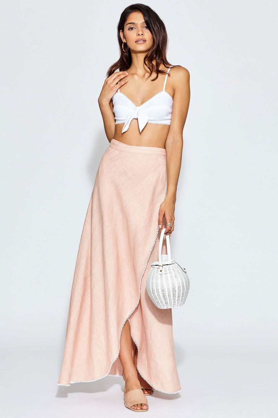 This is a photo of a woman wearing a white, crochet trimmed, linen bralette that ties in the front. She is wearing this with a pastel pink, linen wrap skirt and is holding a white basket bag.