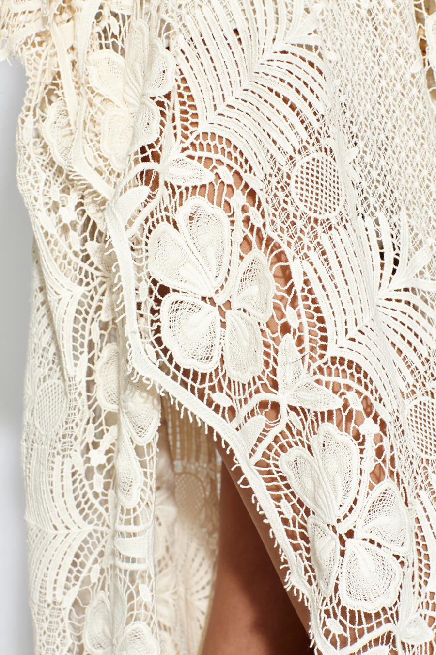 This is a detail photo of natural colored lace on a caftan. The lace detail shows flowers with pineapple and palm details.
