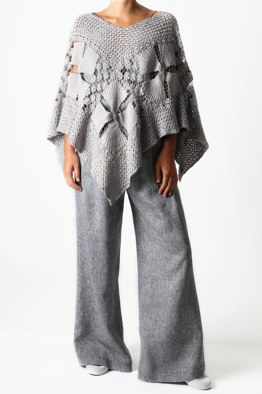 This is a photo of a woman wearing an all grey outfit with grey linen pants and a handmade grey knit shawl in the shape of a poncho.