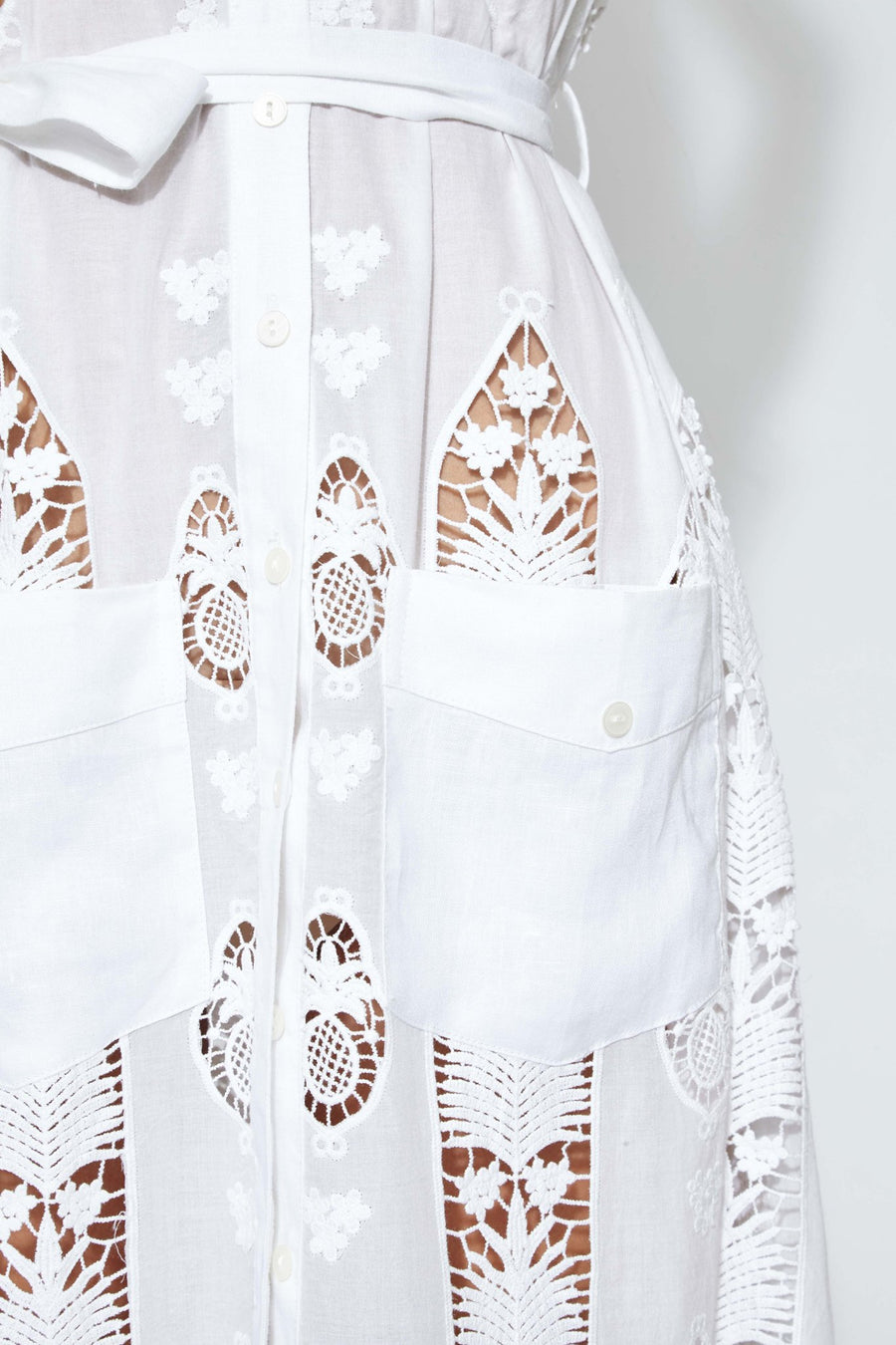 This is a detail photo of square pockets on the front of a white cotton embroidered dress. The pockets fall below the waist and lace design shows small flowers and pineapples.