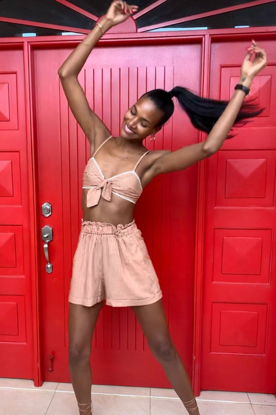 This is a photo of a woman dancing with her arms in the air, wearing a high waisted pair of venetian striped shorts and matching bralette. She stands in front of a red door.