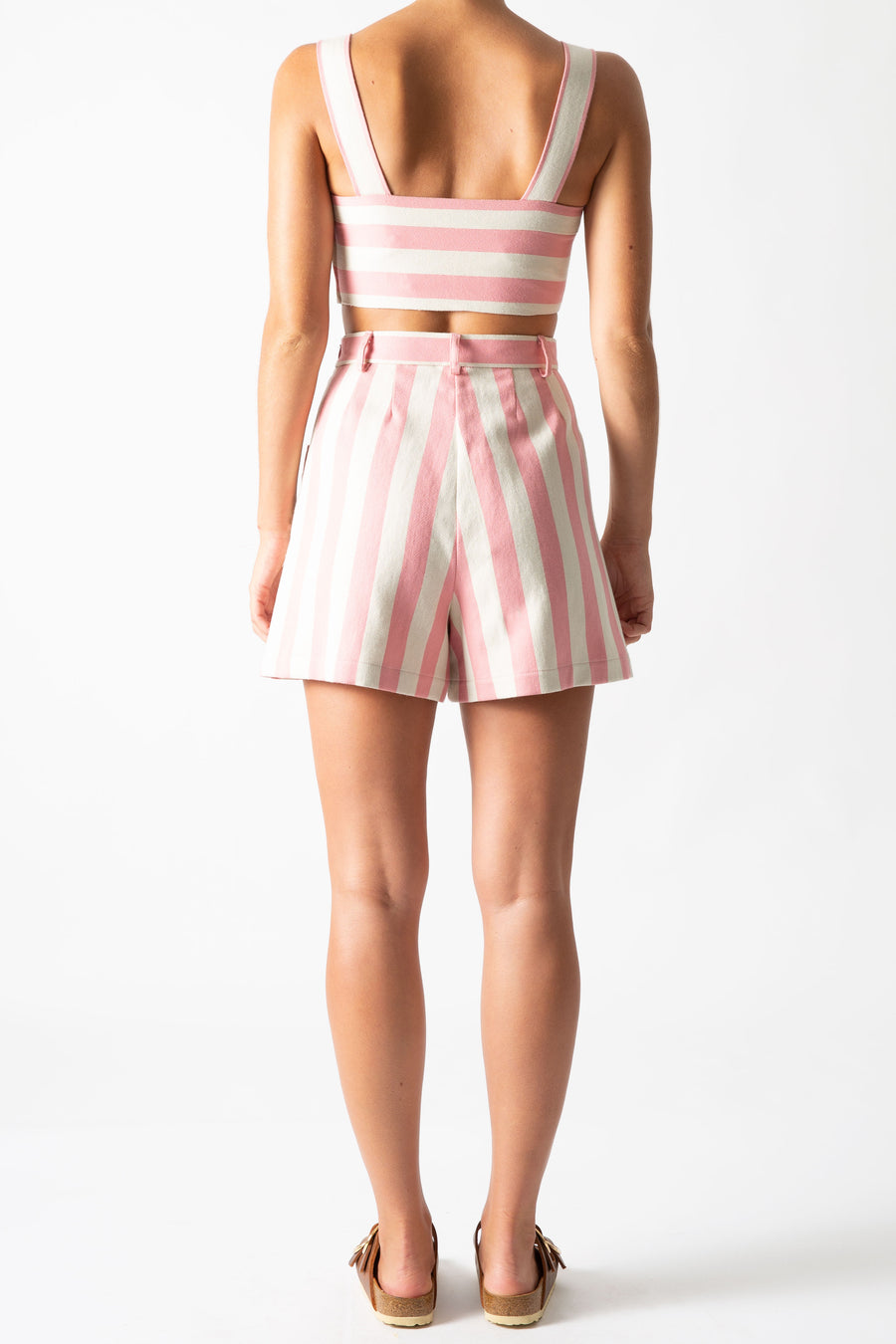 This is a back view photo of a woman wearing a matching two-piece suit with shorts and a cropped top,. The outfit is pink and neutral thick stripes with gold buttons.