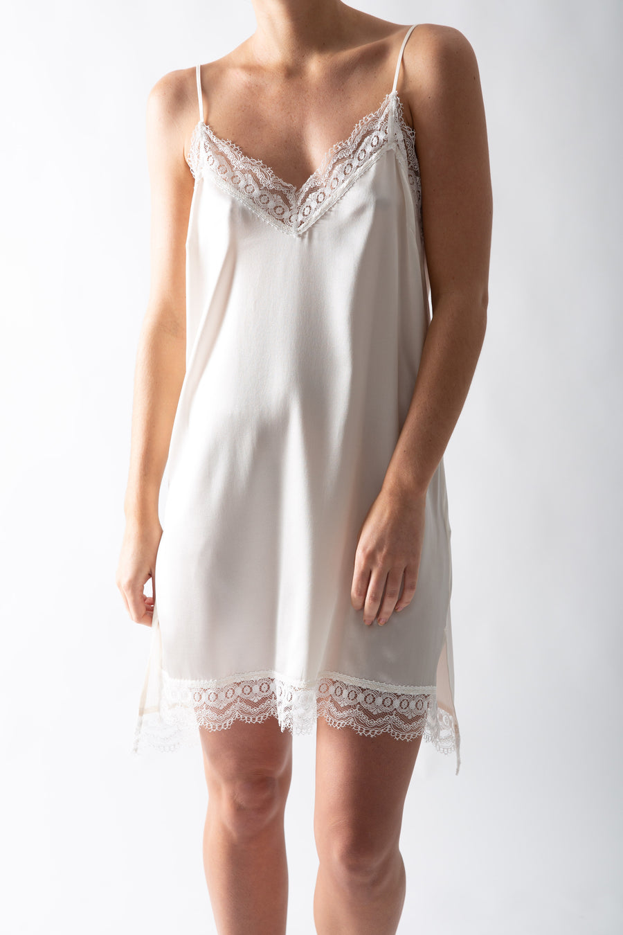 This is a photo of a woman from the neck down, wearing an ivory silk slip dress.
