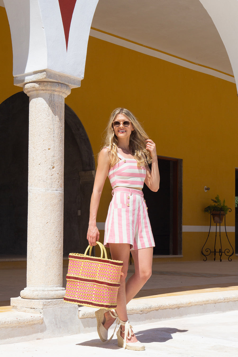 This is a photo of a woman wearing a matching two-piece suit with shorts and a cropped top,. The outfit is pink and neutral thick stripes with gold buttons. She stands in front of a yellow wall and holds a pink and yellow oversized woven tote bag.