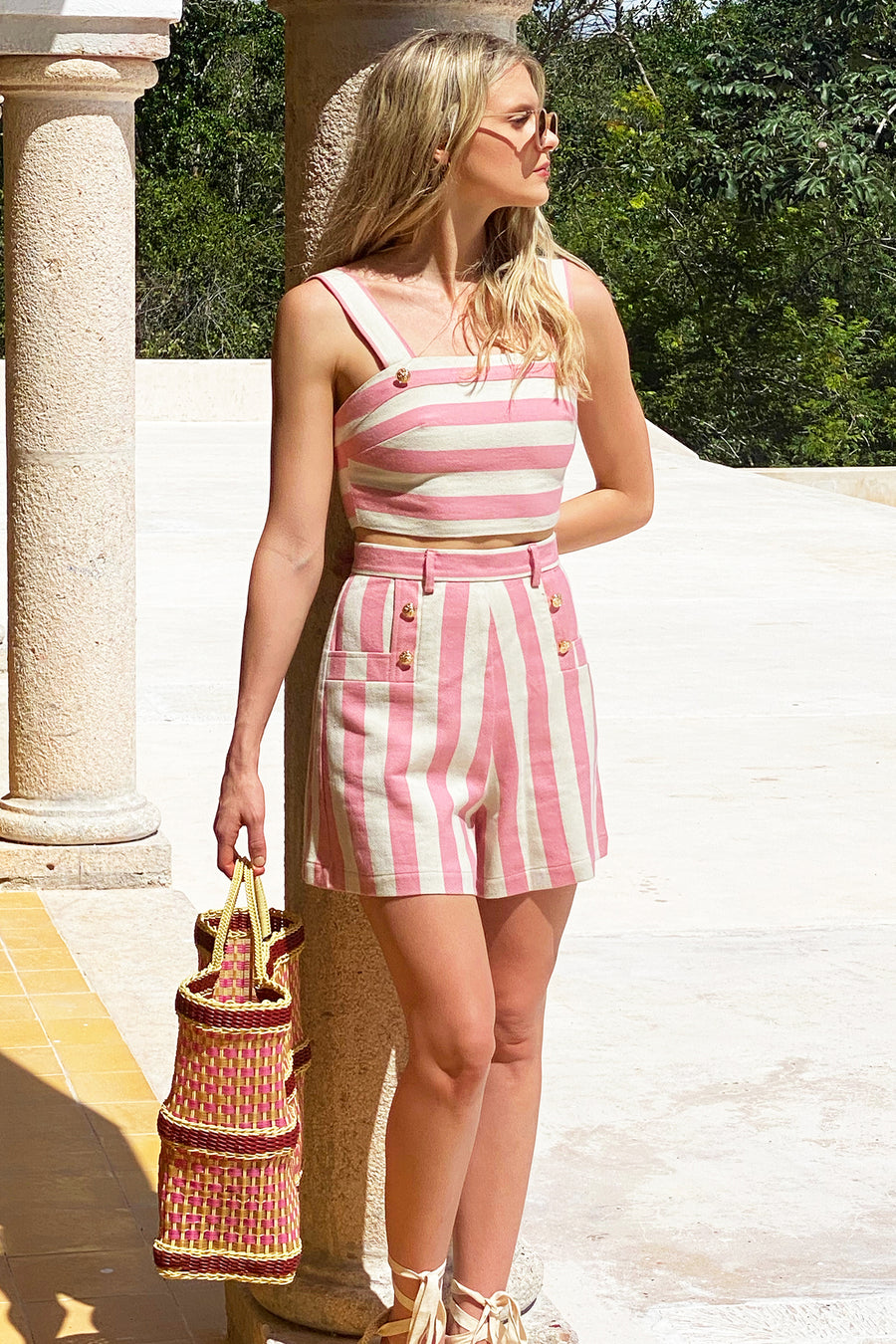 This is a photo of a woman wearing a matching two-piece suit with shorts and a cropped top,. The outfit is pink and neutral thick stripes with gold buttons. She leans against a cement post.