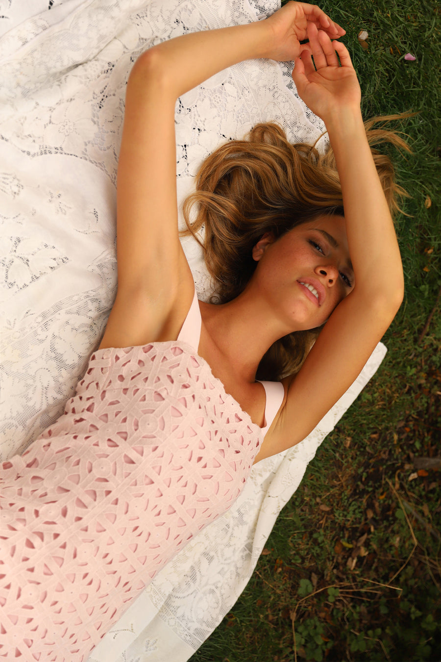 This is a photo of a woman wearing a mini pink lace dress with ribbon straps. She lays on a lace blanket in the grass.