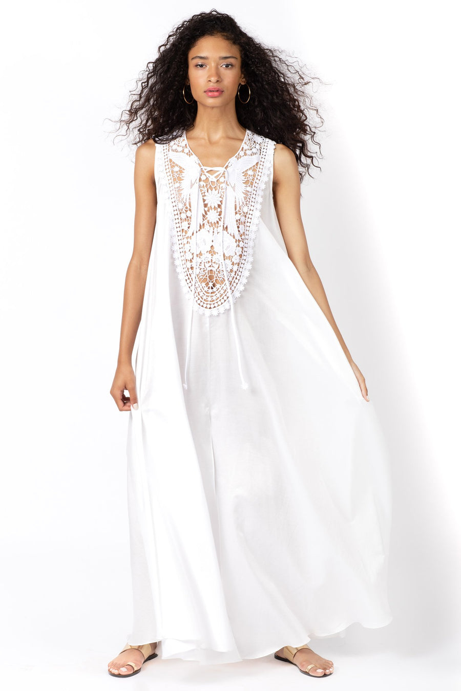 This is a photo of a woman wearing a floor length, pure white, kaftan dress. The dress features a large, embroidered yolk at the center front neckline, which depicts two birds surrounded by flowers.