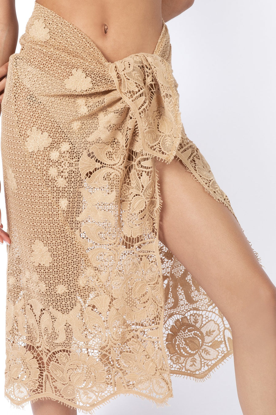 This is a close-up photo of the lace scalloped pareo tied around the model's waist.