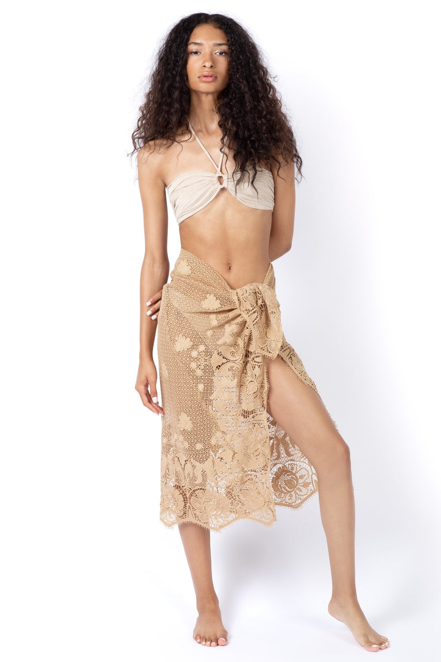 This is a photo of a woman wearing a beige colored, halter swim suit top with a lace scalloped, sheer pareo that is tied around her waist.