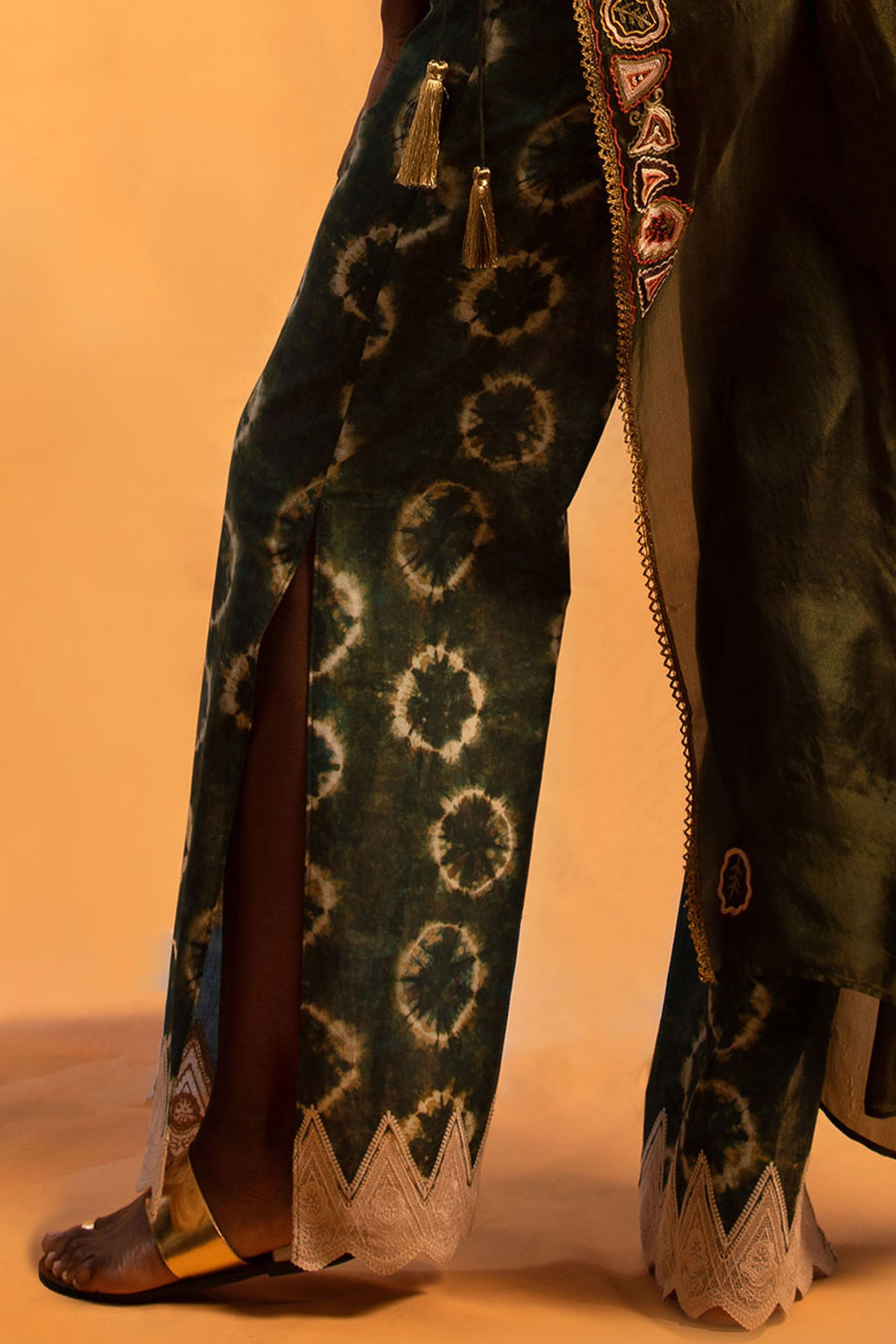This is a detail photo of the side slit on a pair of tie-dye inspired shibori printed pants. The hemline of the pant is a natural colored lace embroidery.