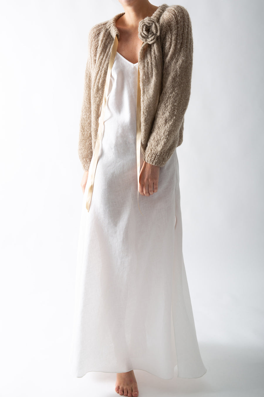 This is a photo of a woman wearing a white linen slip dress with a handmade pleated brown khaki colored cardigan. The cardigan is worn open and has a flower pin on one shoulder.