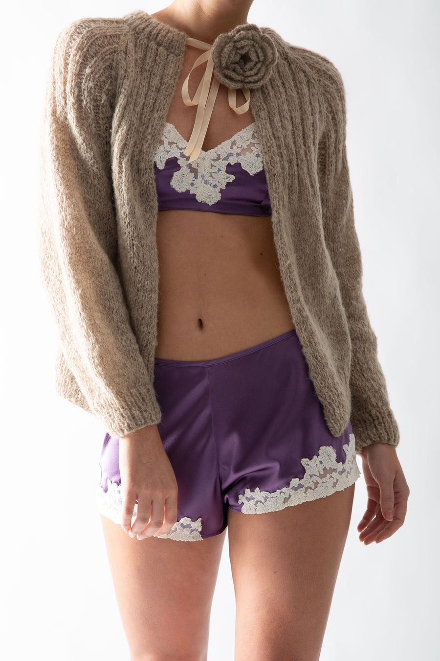 This is a photo of a woman wearing a purple silk bra and shorts with a handmade pleated brown khaki colored cardigan. The cardigan is worn tied at the neck and has a flower pin on one shoulder.