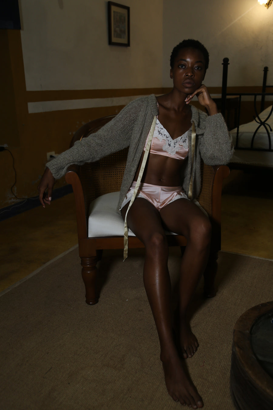 This is a photo of a woman sitting in a chair, she is wearing a knit cardigan on top of a pale pink silk bralette and shorts.