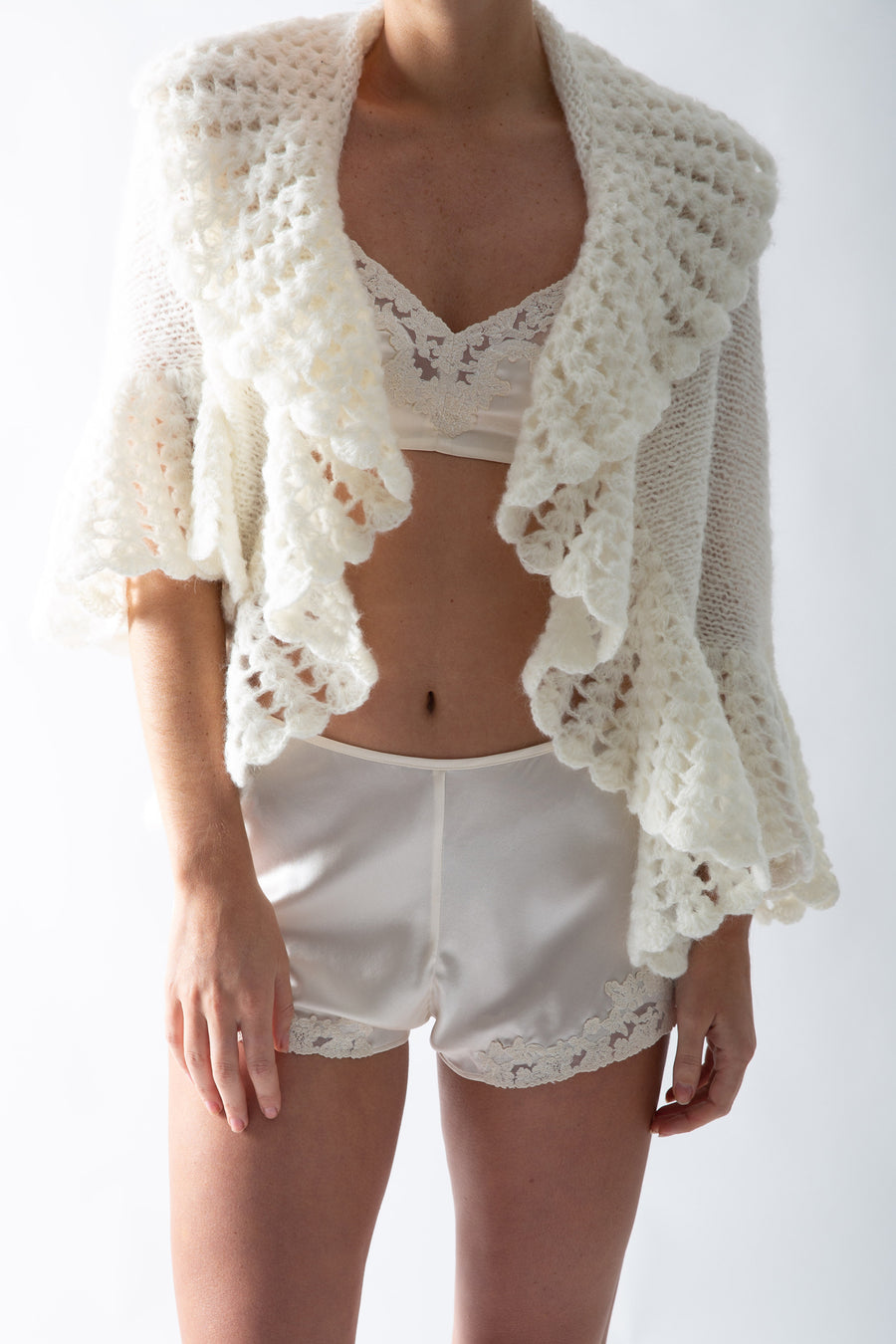 This is a photo of a woman wearing an ivory silk set of mini shorts and bralette with lace trim. She wears a white knit cardigan over top.