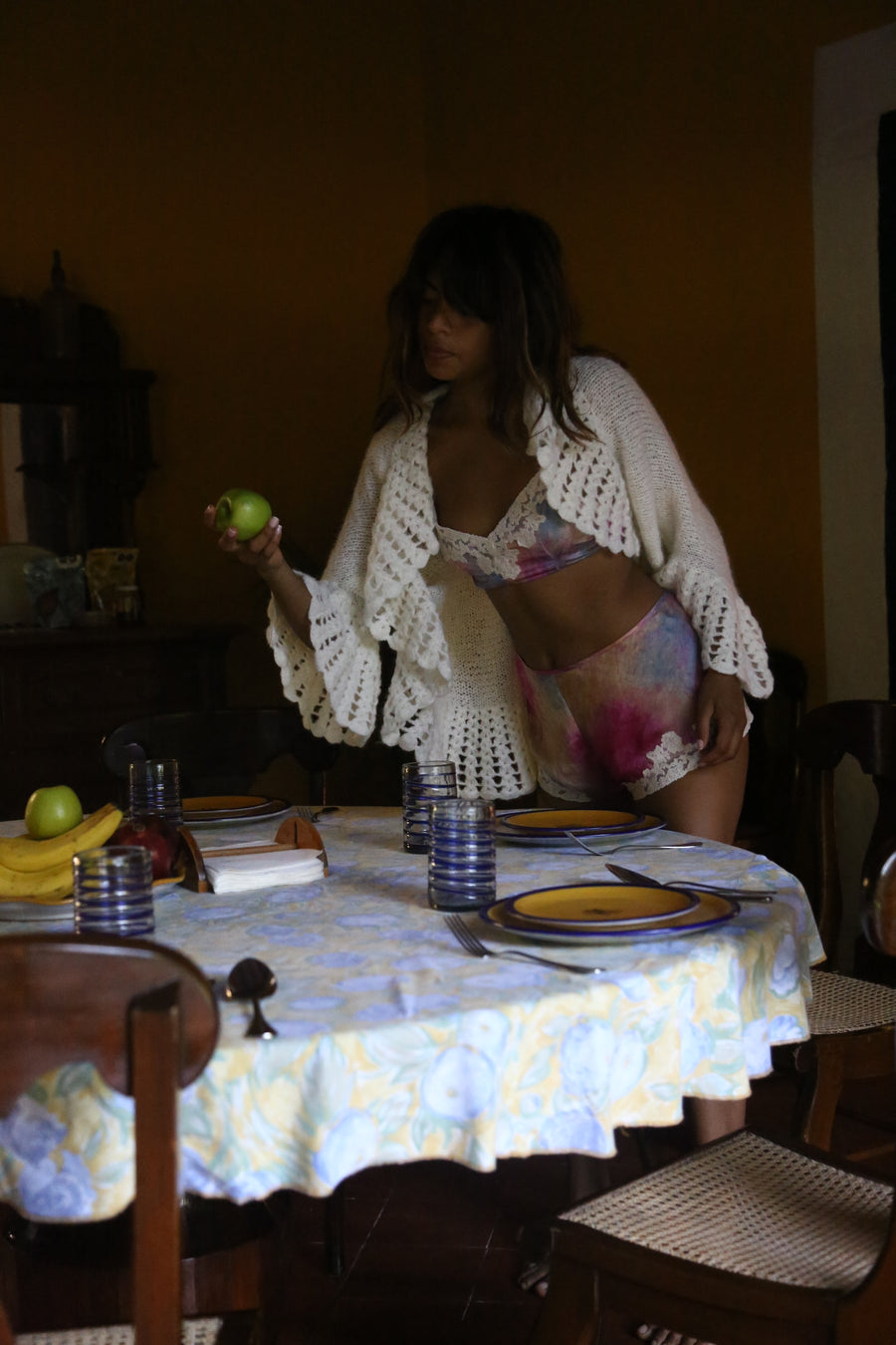 This is a photo of a woman in a ruffled carigan and tie dye print silk bralette and shorts set. She is reaching over a table to grab an apple.
