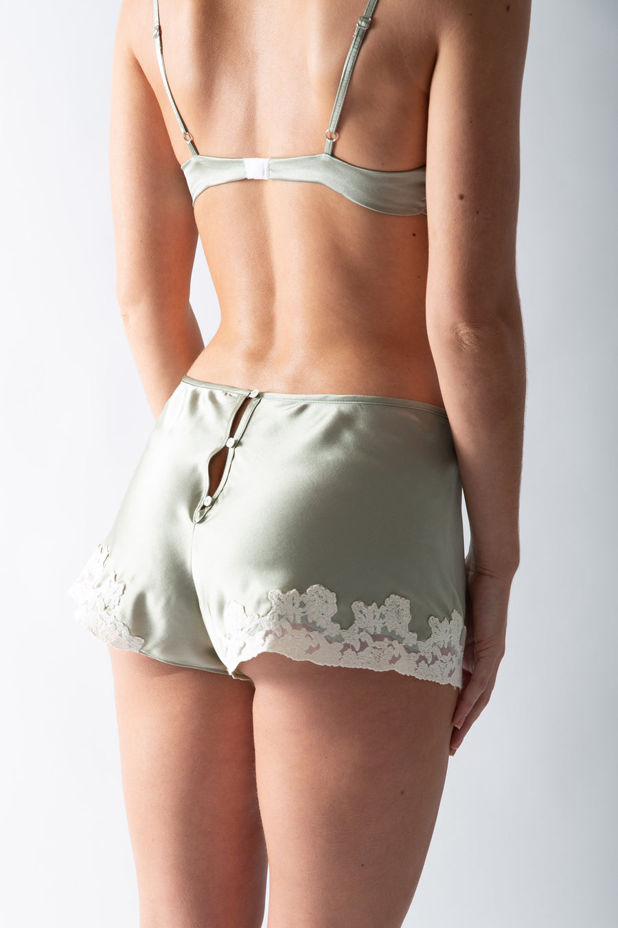This is a back photo of a woman wearing a sage colored silk set of mini shorts and bralette with lace trim. The back of the shorts have 3 button closure up the center back.