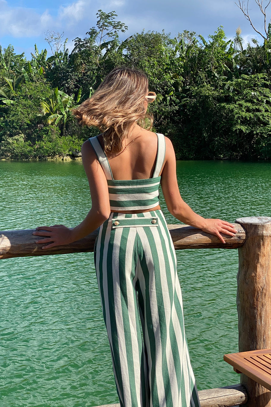 This is a photo of a woman wearing a matching two piece green striped set with gold buttons.  The pants are high waisted and long with a flare and the top is cropped with straps. She looks to the water behind her from a dock.