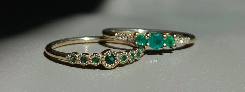 Two Jennie Kwon emerald rings shot in shadow