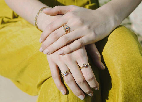 Jennie Kwon UK - Model wearing multiple Jennie Kwon rings on both hands against yellow trousers