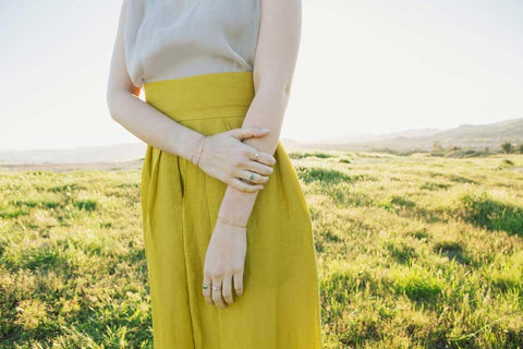 Jennie Kwon model wearing rings and bracelets on both hands in sunny field