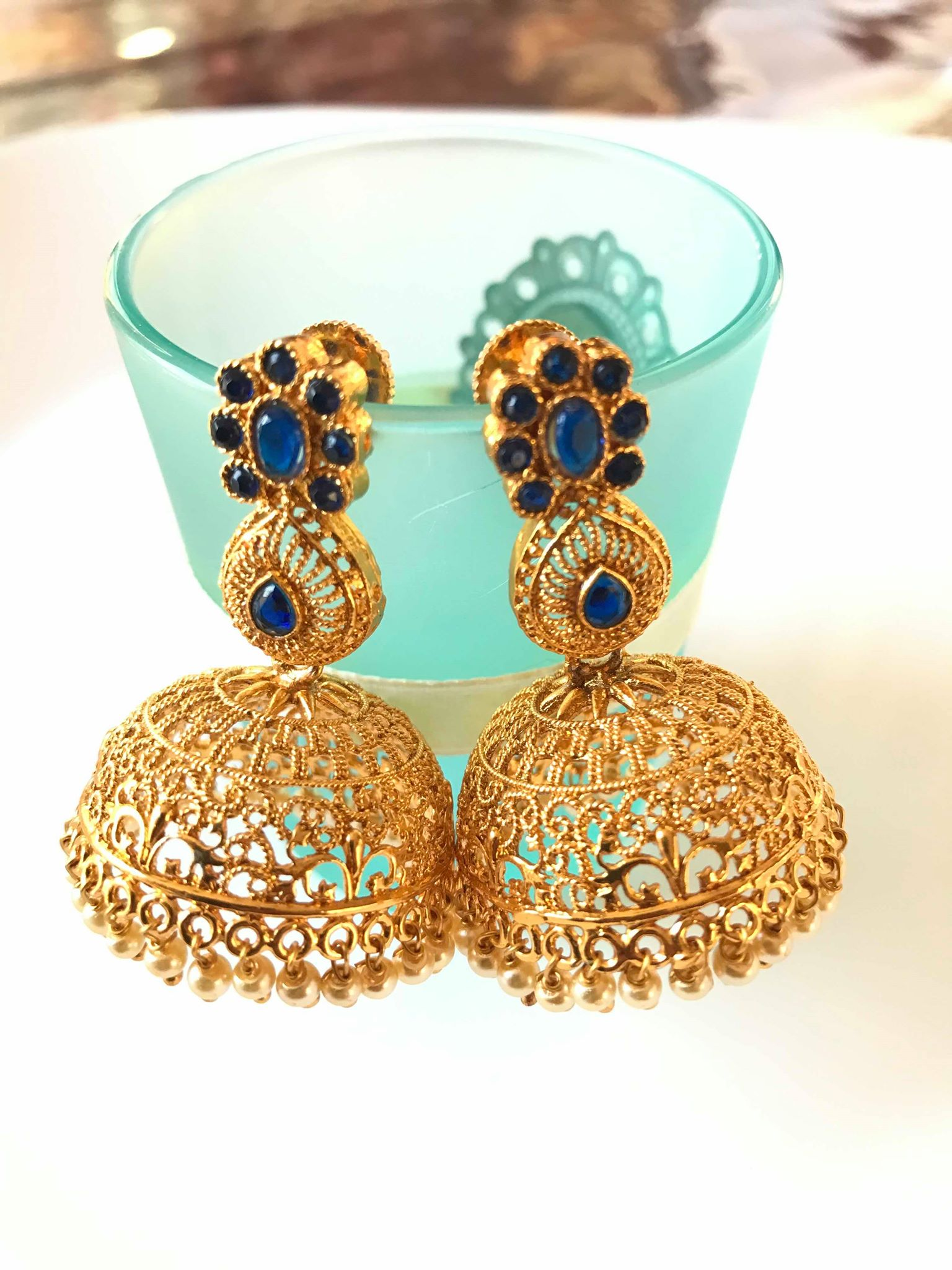 Gold Colored Jhumka Earrings with Blue Stones