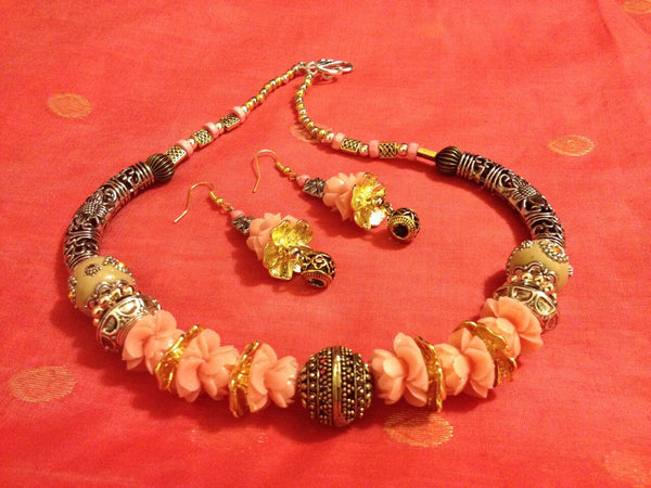 Golden and Silver metal Choker set with salmon color lotus beads  makes this unusual combination urban and chic. A must collectable comes with matching earrings.