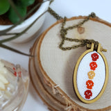 red orange and yellow cross stitch skull necklace