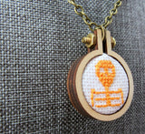 orange cameo skeleton cross stitch necklace