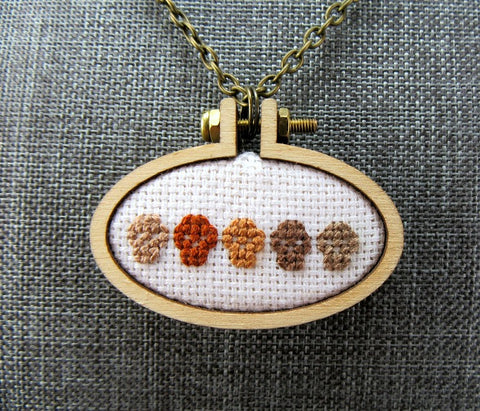 sepia tiny skulls cross stitched necklace