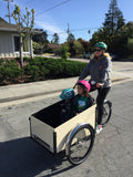 picture of blond woman in green helmet riding cargo bike/trike. in the Cargo box are two small children-on the left side of box is a girl in a pink helmet, and to her right is a smaller boy in a teal colored helmet. The sky is blue. The sun is shining.