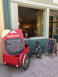 Picture of Cargo bike/trike with red painted cargo box parked on sidewalk in front of cake shop. there is a chalk board shaped like a fairytale cabin in the box with the days specials written on it in colorful chalk.