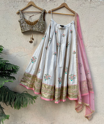 Off-white raw silk lehenga with colourful embroidery