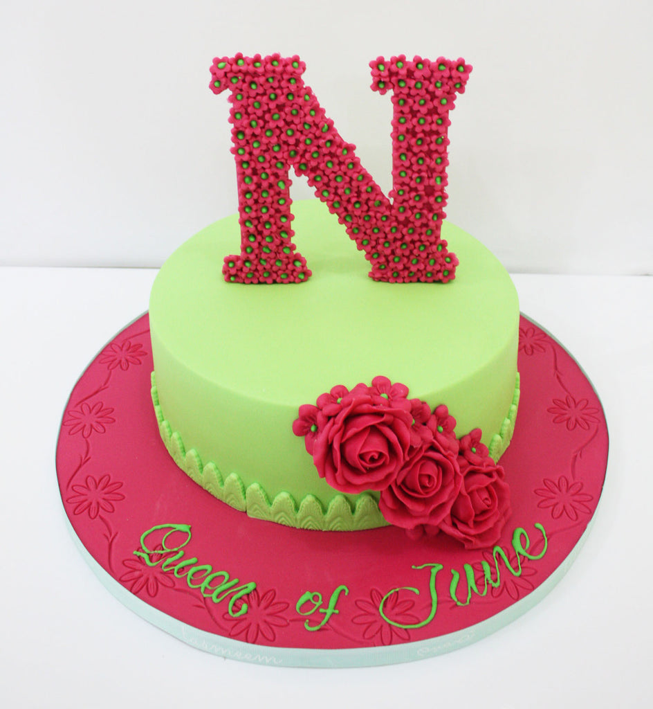 Round Cake With Flower Letter On The Top Tasmeem