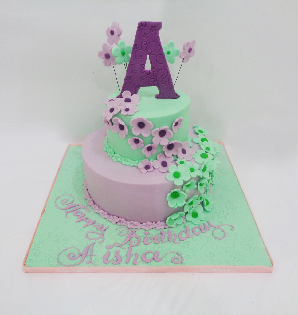 Two Tiered Cake With Flowers Letter On The Top Tasmeem