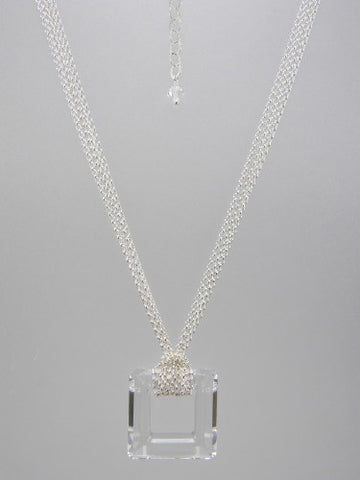 Fine round rolo link sterling silver chain layered and knotted around 30 mm square clear crystal ring pendant.