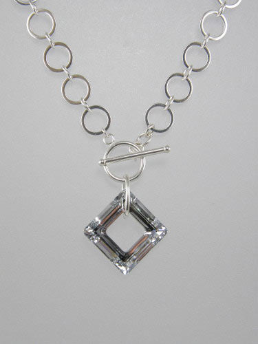 Sterling silver chain with 10 mm flat circle links and front toggle with silver square crystal ring pendant.