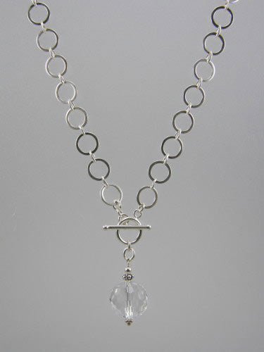 Sterling silver chain with 10 mm flat circle links and front toggle with 16 mm crystal ball pendant. Length of chain is 17 inches.