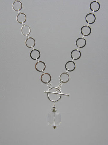 Sterling silver chain with 10 mm flat circle links and front toggle with 12 mm crystal cube pendant.