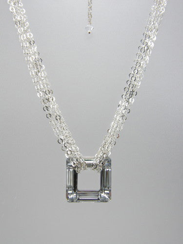 Flat round sterling silver chain triple-wrapped around 30 mm square silver crystal ring pendant.