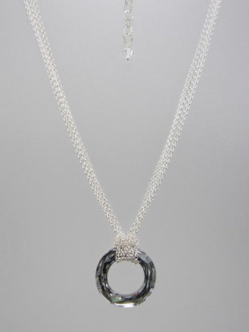 Fine round rolo link sterling silver chain layered and knotted around 30 mm round silver crystal ring pendant.