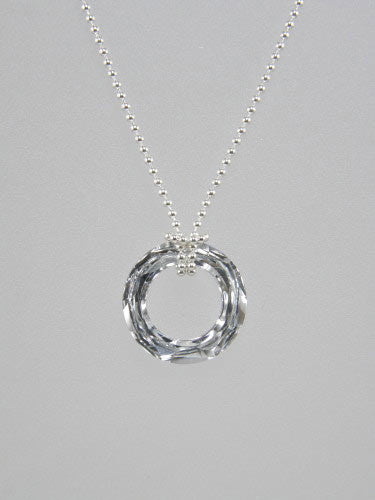 Sterling silver thin ball or rolo chain is knotted around round crystal ring pendant