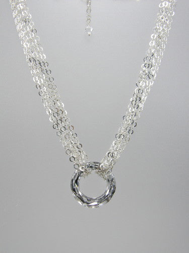 Flat round sterling silver chain triple-wrapped around 30 mm round silver crystal ring pendant.