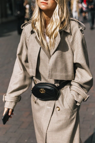 Girl using bum bag as trench coat belt