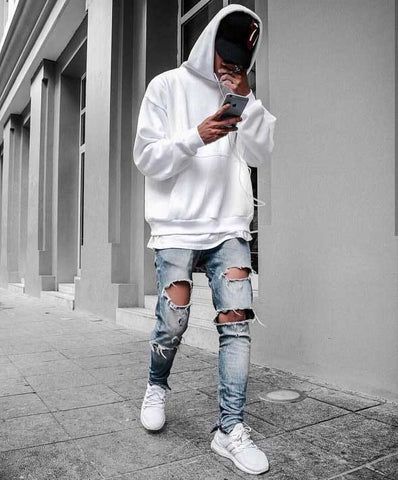Streetwear outfit with white hoodie, ripped jeans, white trainers
