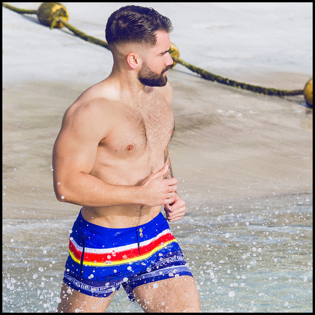 Frontal view of a sexy male model wearing men's beach shorts by the Bang! Clothes brand of men&