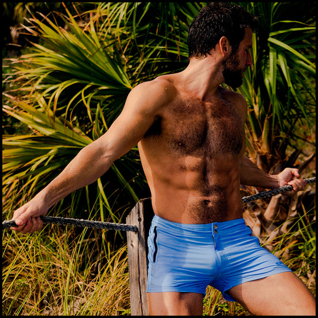 Frontal view of a sexy male model wearing men's beach shorts in blue color by the Bang! Menswear brand from Miami.