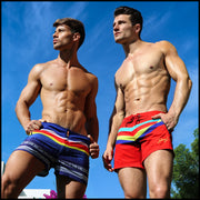 Right side view of a hot male model wearing men's beach trunks by Miami-based Bang! Men's beachwear brand.