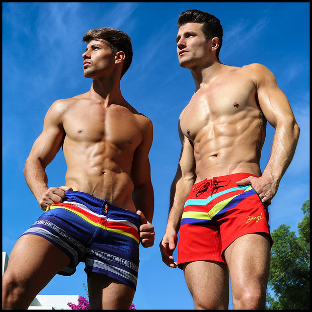 Right side view of a hot male model wearing men's beach trunks by Miami-based Bang! Men&