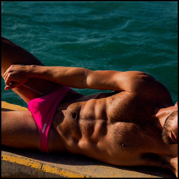 Frontal view of a hot male model wearing a premium men's swim mini brief by the Bang! Clothes company in Miami, Florida. This bathing suit features premium quality fabrics and bold colors